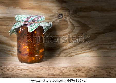 Jar of south Indian homemade vegetable pickle on wooden kitchen table
