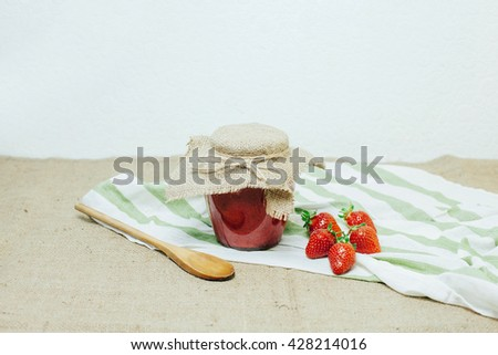 Jar of strawberry jam on the table - stock photo