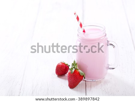 jar of strawberry smoothie on wooden table - stock photo