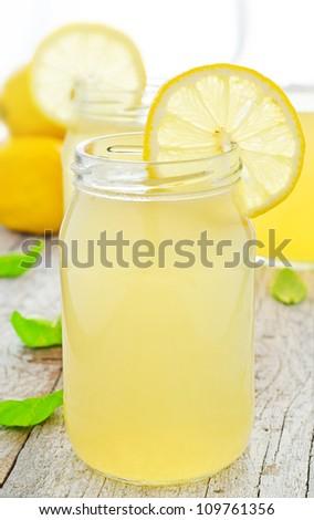 Jar of tasty fresh lemonade with lemons in background - stock photo