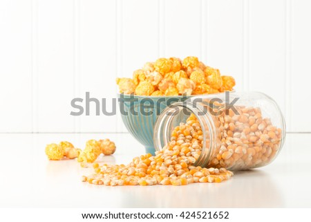 Jar of uncooked popcorn with a bowl of popcorn in the background. - stock photo