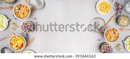 Jar salads preparation with vegetables and ingredients on gray tone background, top view, banner. Healthy and clean eating or diet food concept - stock photo