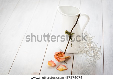 Jar with a dried rose on a white wooden background.