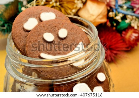 Jar with biscuits and dried flowers on table - stock photo