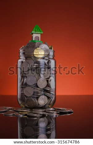 Jar with full of coin and small house  model concept