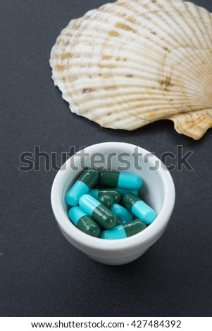 Jar with heap of blue green round capsule pills with medicine antibiotic - stock photo