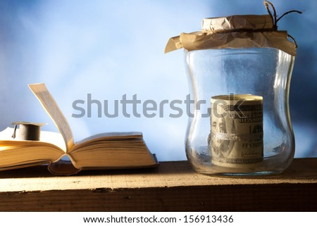 Jar with money, college graduation cap and open book.  - stock photo