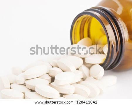 Jar with pills on white background
