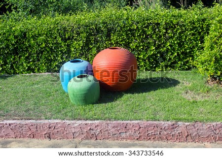 Jars in a large colorful beautiful pattern put on green grass
