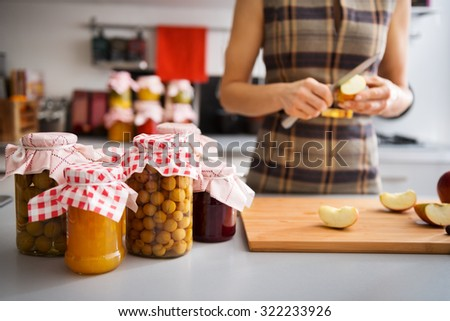 Jars of freshly-preserved fruits are standing on a counter, ready to be put away for the winter. In the background, an elegant woman is quartering more apples. - stock photo