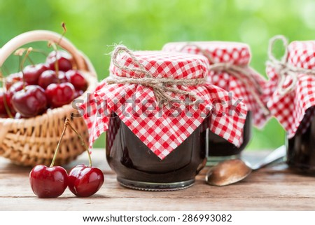 Jars of jam and basket with cherry. - stock photo