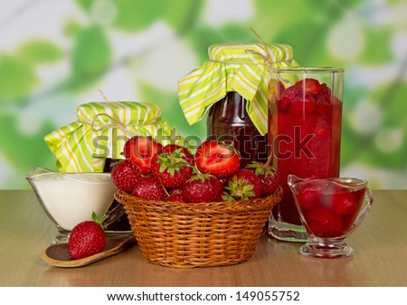 Jars of jam, cup with cream, basket with strawberry and spoon on a table