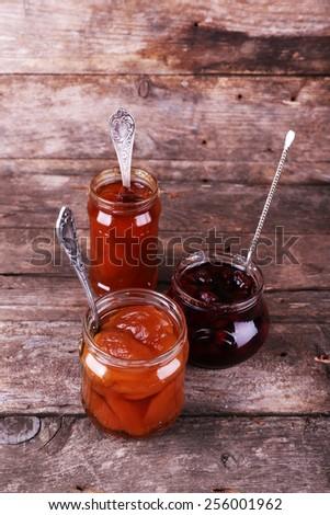 Jars of tasty jam on wooden background - stock photo