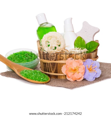 Jars with body care cosmetics in wooden basket, sea salt in wooden spoon and flowers on hessian cloth napkin, white background - stock photo