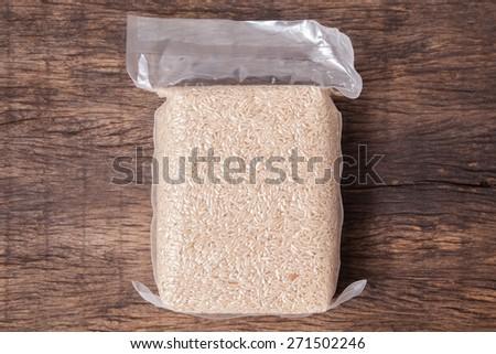 Jasmine brown rice in vacuum plastic bag package on wooden table top - stock photo