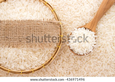 Jasmine rice in a wooden spoon on rice background with blank label of natural sackcloth - stock photo