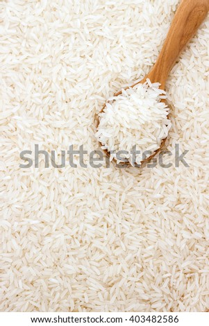 Jasmine rice in a wooden spoon on rice background with copy space - stock photo