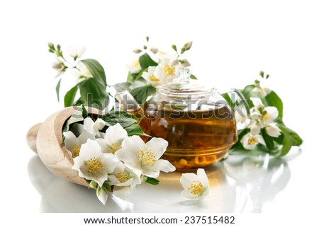 jasmine tea in a teapot with a branch of jasmine on a white background
