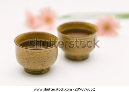 Jasmine tea in traditional Japanese tea cup with pink flowers in the background - stock photo