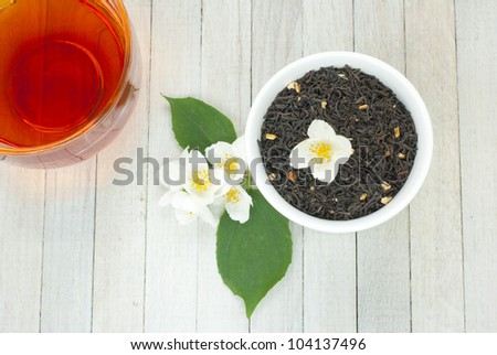 jasmine tea with jasmine flowers on wooden background - stock photo