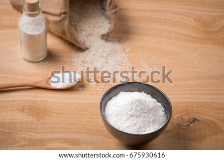 Jasmine white rice in sack and rice flour on wooden table.