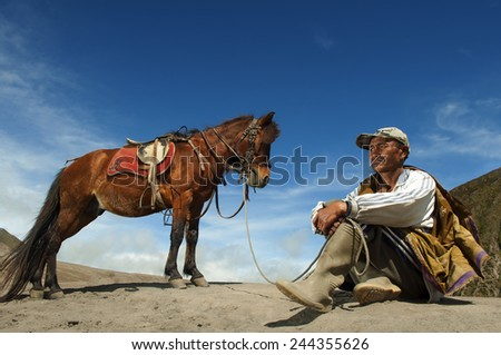 JAVA,INDONESIA-April 9 :Indonesia man with the horse for tourist rent at Mount Bromo on April 9,2014 in Java , Indonesia.Mt. Bromo is an active volcano and part of the Tengger massif, in East Java. - stock photo