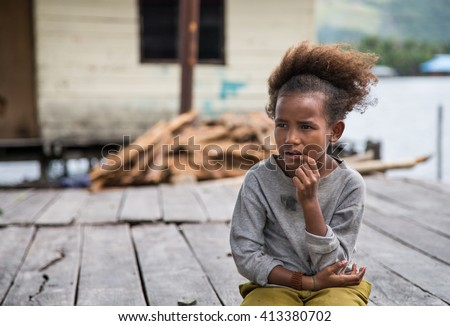 JAYAPURA, WEST PAPUA, INDONESIA - CIRCA FEBRUARY 2016: Papuan girl sitting with a dreamy face