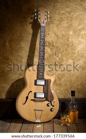 jazz guitar with bourbon bottle - stock photo