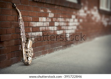 Jazz musical instrument saxophone with grungy street background - stock photo