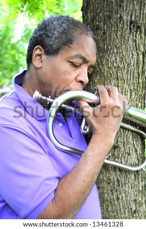 Jazz musician in the woods. - stock photo