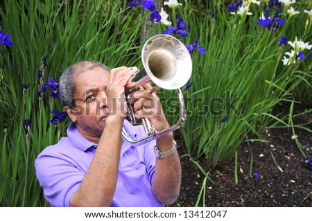 Jazz musician performing in a flower garden on his instrument. - stock photo