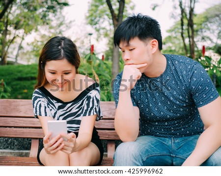 Jealous boyfriend peeking and spying his girlfriend mobile phone while she is reading a message - stock photo