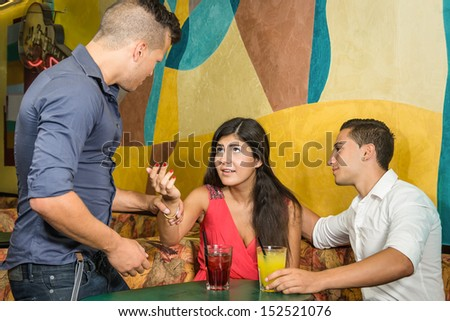Jealous Boyfriend recovering his Girlfriend from another Boy - stock photo