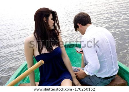 Jealous girlfriend observing boyfriend - stock photo