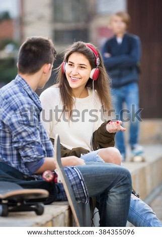 Jealous teen and his smiling friends after conflict outdoors  - stock photo