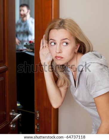 Jealous wife, overhearing a phone conversation her husband - stock photo