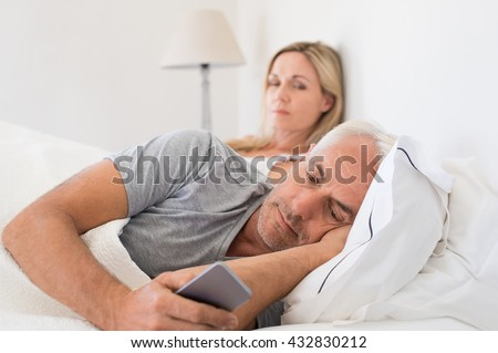 Jealous woman spying her husband mobile phone while he is reading a message. Senior couple in bed while wife is angry as husband using smartphone. Husband ignoring wife and texting on smartphone.  - stock photo