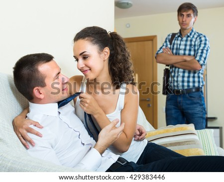 Jealous young husband discovering his attractive wife cheating him with lover