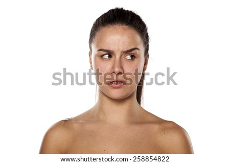jealous young woman without makeup looking aside - stock photo