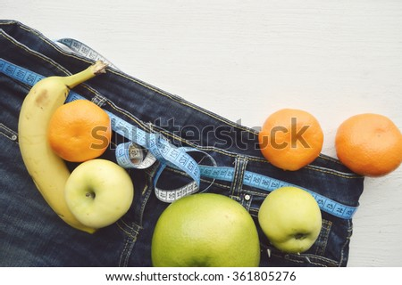 Jeans and a measuring tape.Concept of loosing weight.fruits for weight loss - stock photo