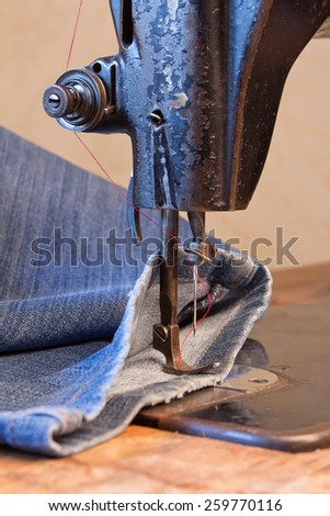 jeans and a vintage sewing machine - stock photo