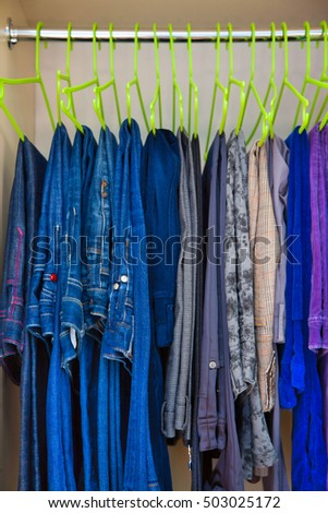 Jeans and pants hung on hangers in the wardrobe. Hangers in a row.