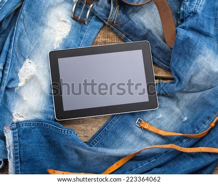 Jeans around mobile tablet pc on old wooden background - stock photo