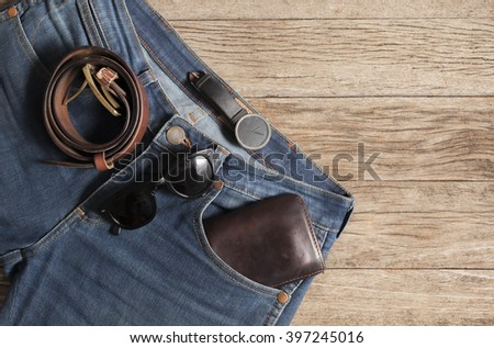 Jeans Wallet and Belt watches glasses  on wood background,top view - stock photo