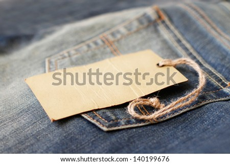 Jeans with blank paper price tag - stock photo