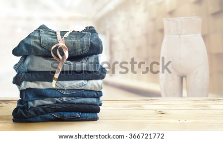 jeans with measure  in shop on wooden shelf and interior of fashion clothes store  - stock photo