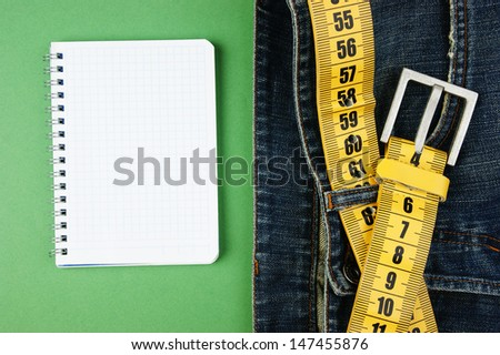 jeans with meter belt slimming and notebook on the green background - stock photo