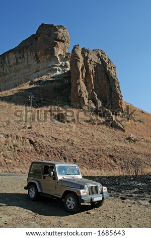 Jeep parked infront of a rock formation - stock photo