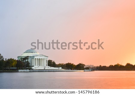 Jefferson Memorial silhouette at sunrise with mirror reflection on water, Washington DC United States