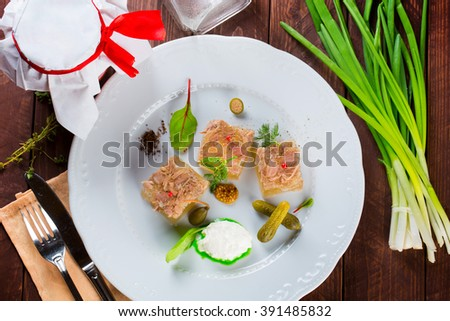 Jellied meat on plate with spices and cucumber